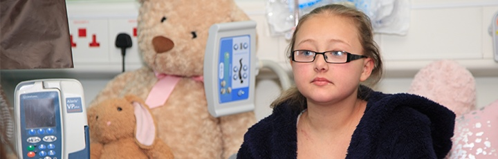 Girl in hospital bed with bear
